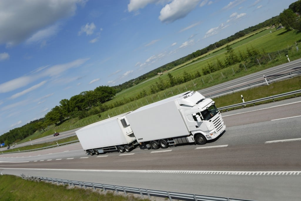 large clean-white truck speeding on highway with countryside pan